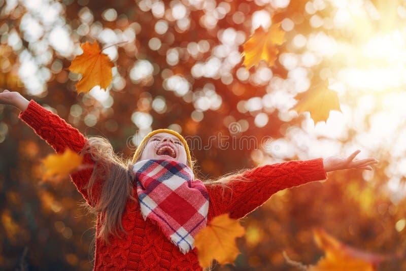 Kind, das mit Herbstlaub spielt lizenzfreie stockfotos