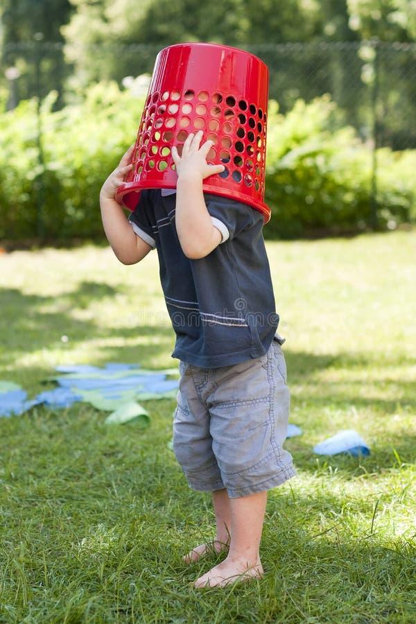 Kind, das mit Korb im Garten spielt lizenzfreie stockfotografie
