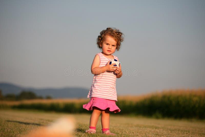 Kind, das mit Kugel spielt stockfotos
