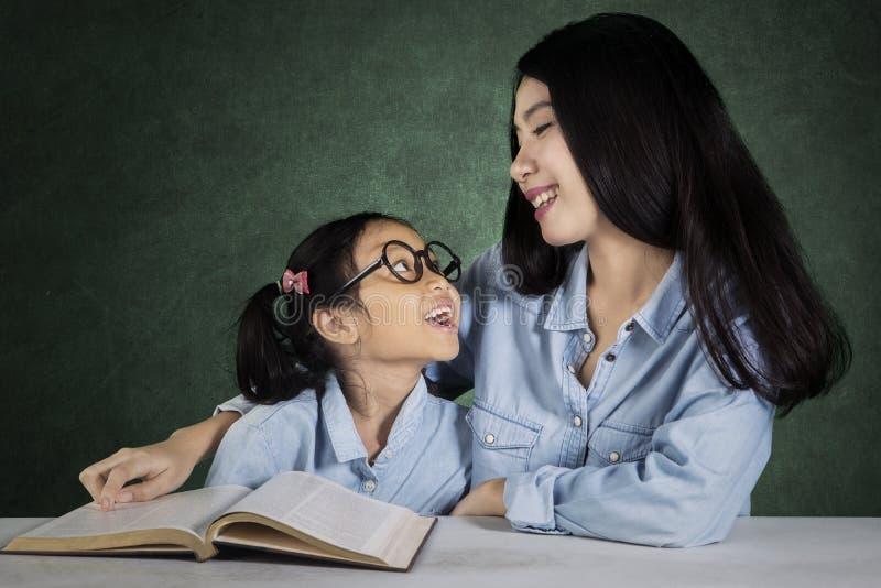 Kind, das mit Lehrer in der Klasse spricht stockfotos