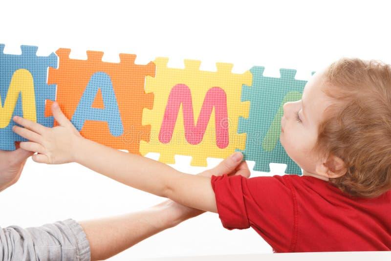 Kind, das mit Puzzlespielblock-ABC-Alphabet, Gegenstand spielt stock abbildung
