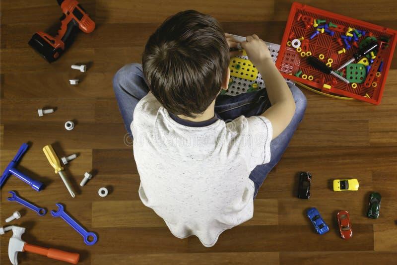 Kind, das mit Spielwarentool-kit beim Sitzen auf dem Boden in seinem Raum spielt Beschneidungspfad eingeschlossen stockfoto