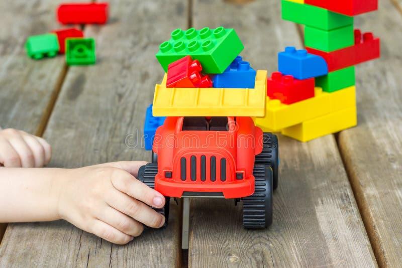 Kind, das mit Spielzeuglastwagen- und Plastikbausteinen spielt stockfotos