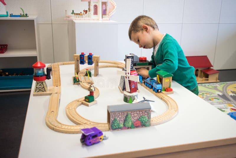 Kind, das mit Spielzeugzug spielt lizenzfreie stockfotografie