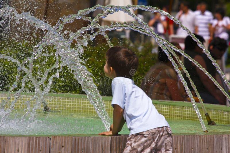 Kind, das mit Wasserbrunnen spielt stockfoto
