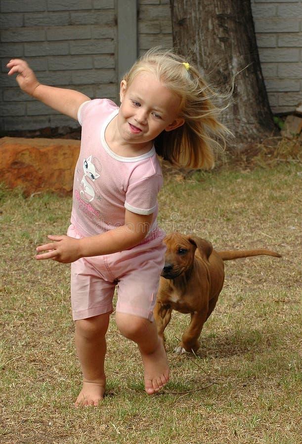 Kind, das mit Welpen spielt lizenzfreie stockbilder