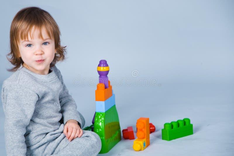 Kind, das mit Ziegelsteinen spielt lizenzfreie stockfotografie
