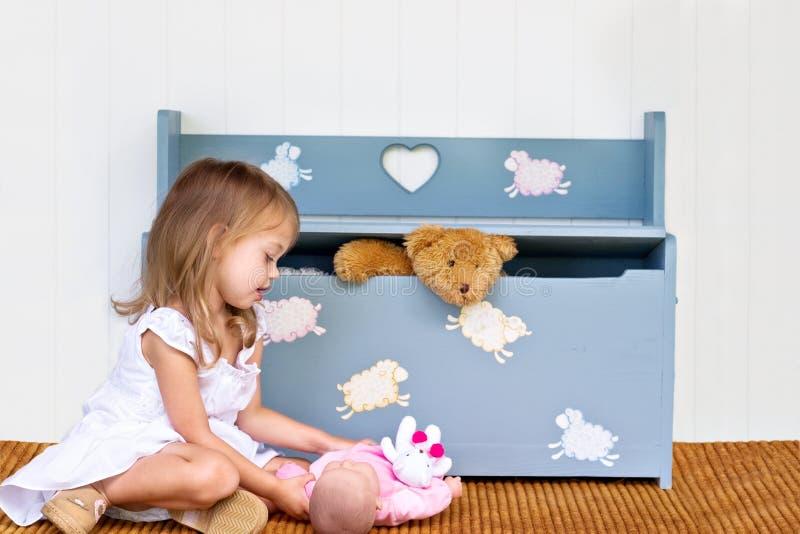 Kind, das nahe Spielzeugkasten spielt. stockbild