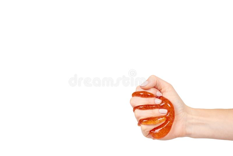 Kind, das orange Schlamm mit der Hand, transparentes Spielzeug spielt lizenzfreie stockbilder