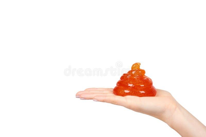 Kind, das orange Schlamm mit der Hand, transparentes Spielzeug spielt stockfotos
