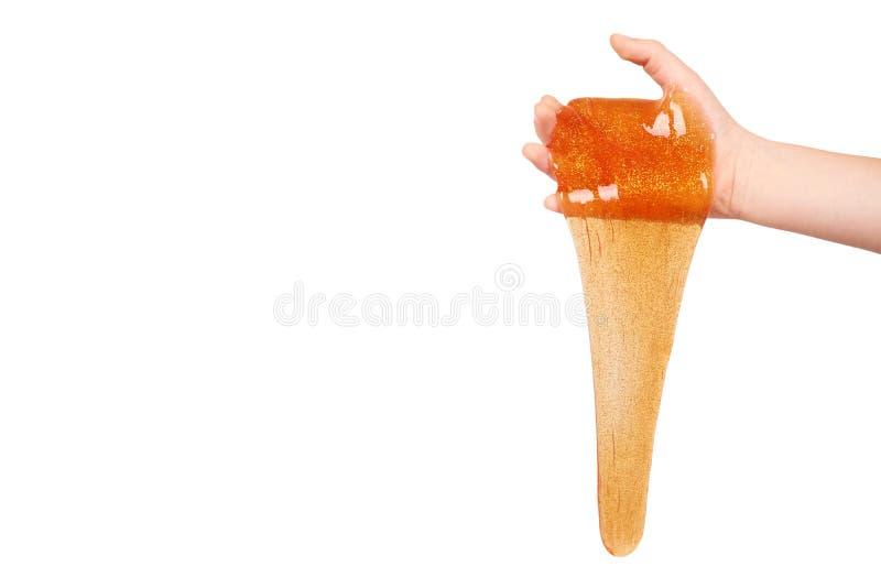 Kind, das orange Schlamm mit der Hand, transparentes Spielzeug spielt lizenzfreies stockbild