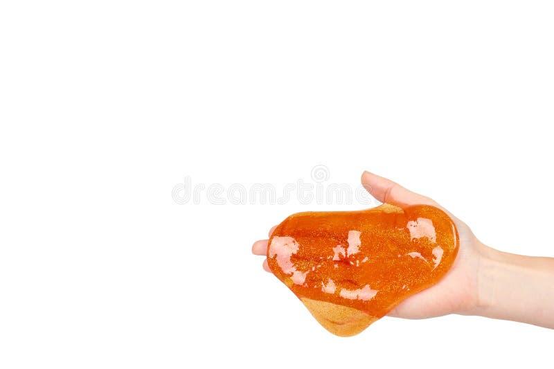 Kind, das orange Schlamm mit der Hand, transparentes Spielzeug spielt stockfoto