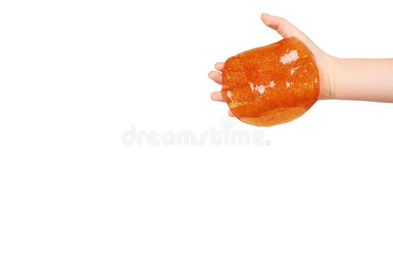 Kind, das orange Schlamm mit der Hand, transparentes Spielzeug spielt stockbilder