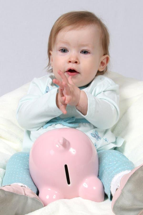 Kind, das Piggy Querneigung und C anhält stockbilder