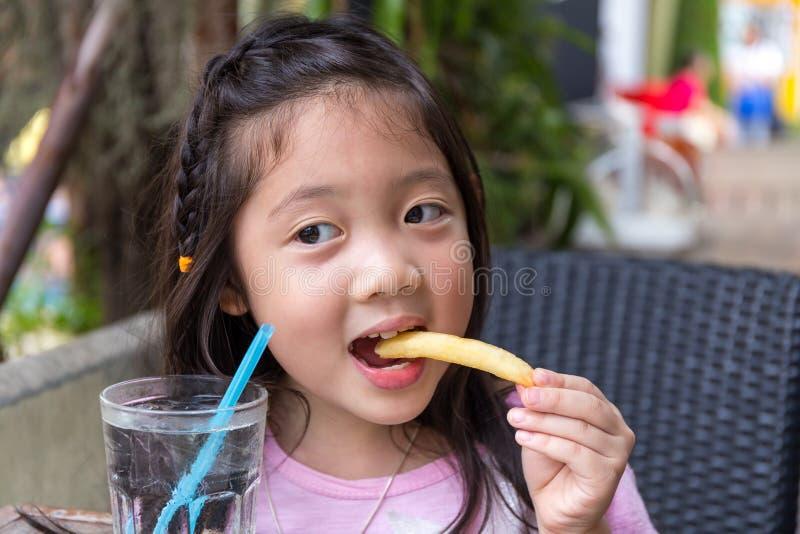 Kind, das Pommes-Frites isst stockbild