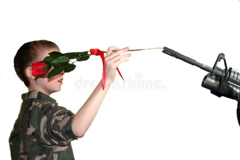 Kind, das Rose in Gewehr 1 legt stockfoto