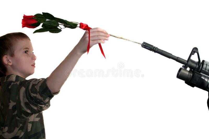 Kind, das Rose in Gewehr 2 legt stockfoto