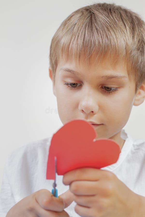 Kind, das rotes Papierherz mit Scheren schneidet stockbilder