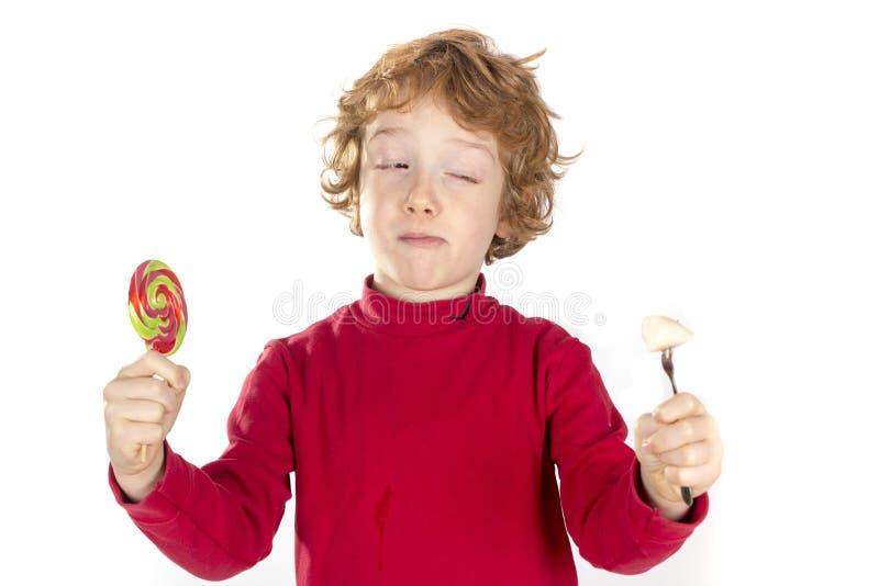 Kind, das Süßigkeit und Frucht hält lizenzfreies stockbild