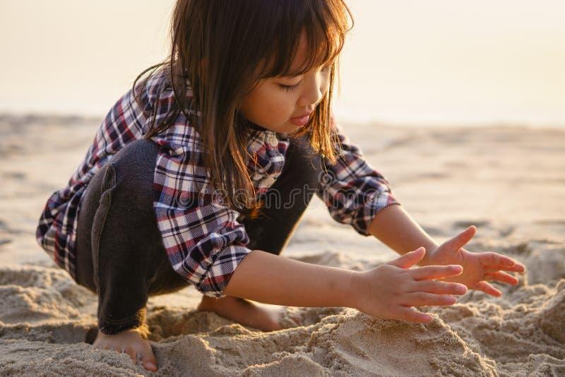 Kind, das Sand am Strand spielt stockfotos