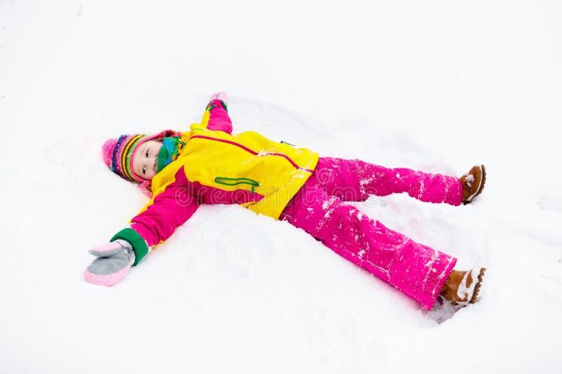 Kind, das Schnee-Engel macht Kinderspiel im Winterpark stockfotos