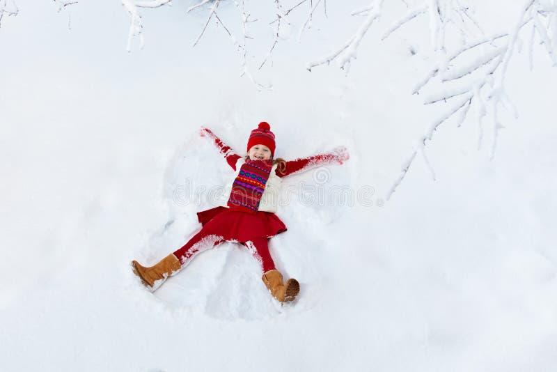Kind, das Schnee-Engel macht Spaß des Kinderwinters im Freien lizenzfreie stockbilder