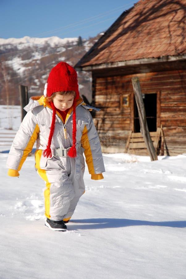 Kind, das in Schnee geht lizenzfreie stockbilder