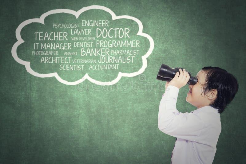Kind, das seinen Traum mit binokularem betrachtet stockfoto