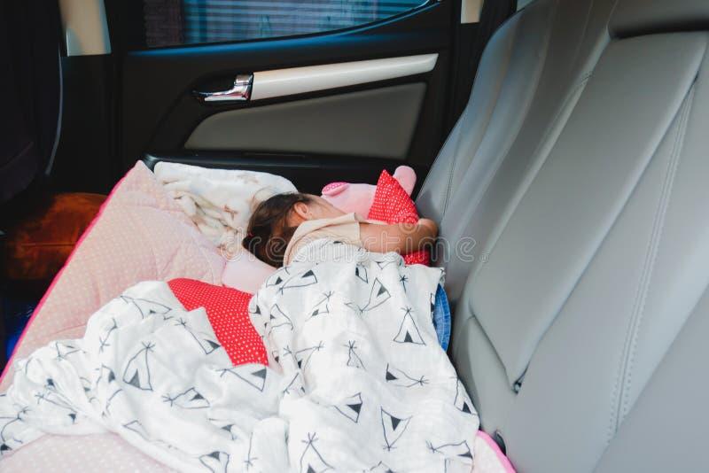 Kind, das sonst innerhalb eines Fahrzeugs ohne eins mit ihr, gefährlich schläft, Ihr Kind im Auto lassend stockfoto