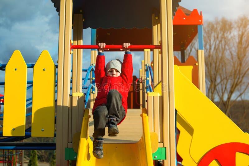 Kind, das Spaß am Spielplatz im Herbst hat Moderner bunter Spielplatz am bewölkten Tag Kindart und weise Scherzt Tätigkeiten Herb lizenzfreies stockfoto