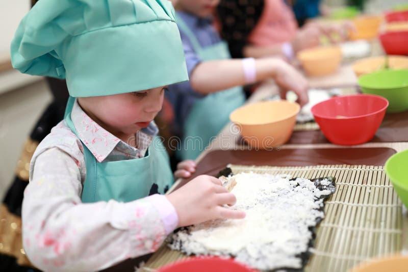 Kind, das Sushibestandteile setzt lizenzfreie stockfotografie