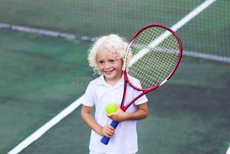 Kind, das Tennis auf Gericht im Freien spielt stockfotos