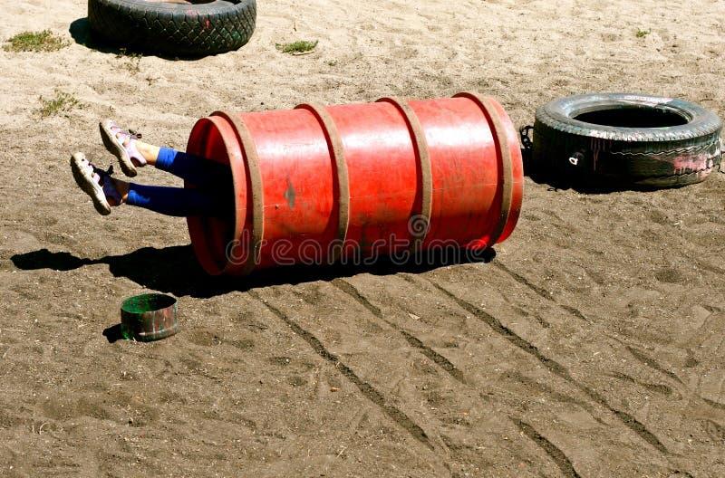 Kind, das unten Hügel im Spielplatz rollt lizenzfreie stockfotos