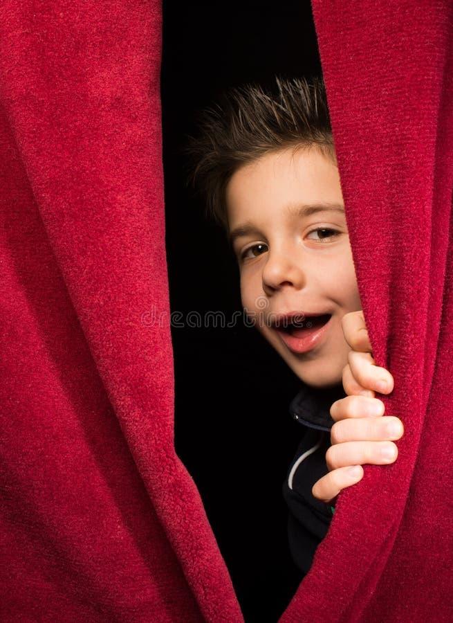 Kind, das unter dem Vorhang erscheint stockfoto