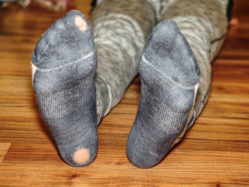 Kind, das verschwitzte Socken mit Löchern in der Ferse trägt stockfoto