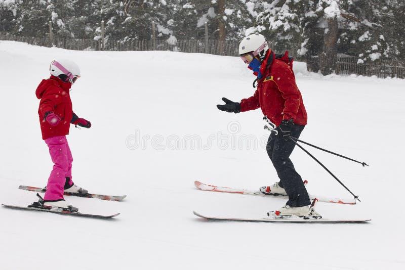 Kind, das wie man mit Monitor lernt, Ski fährt Skispuren im Schnee stockfotografie