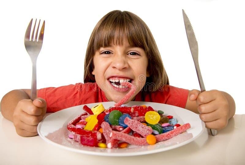 Kind, das wie verrückt Süßigkeit im Zuckermissbrauch und im ungesunden süßen Nahrungskonzept isst lizenzfreies stockfoto