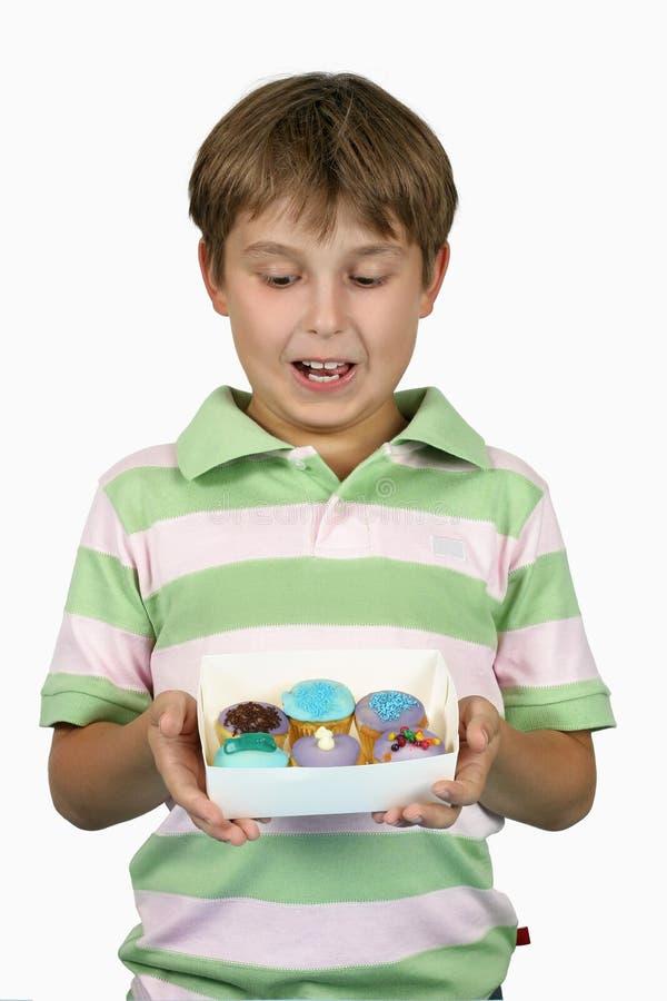 Kind, das yummy kleine Kuchen anhält lizenzfreie stockbilder