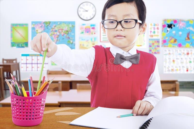 Kind, das Zeichenstift verwendet, um in die Klasse zu zeichnen stockbilder