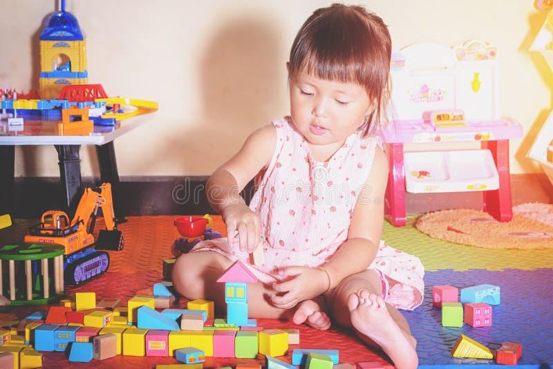 Kind, das zu Hause hölzernen Toy Blocks spielt lizenzfreie stockfotos