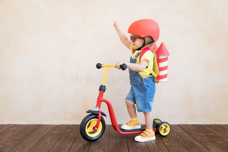 Kind, das zu Hause mit Spielzeugrakete spielt stockbild