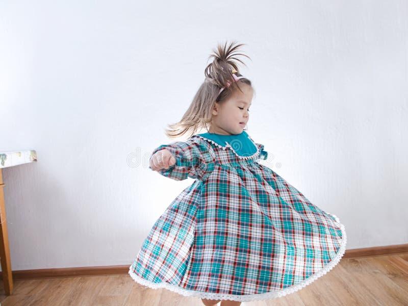 Kind, das zu Hause tanzt inländisches Kind im Kleid, das Rock wirbelt stockfotografie