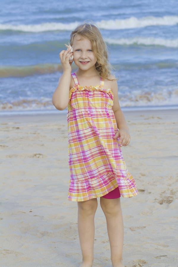 Kind, das zum Shell am Strand hört. lizenzfreies stockfoto