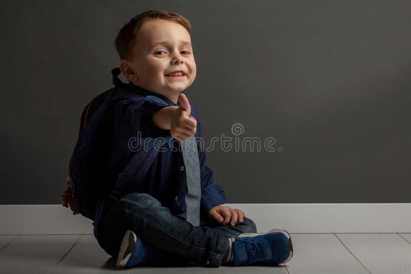 Kind, das zur Schule fertig wird Sitzt auf dem Boden mit einem Rucksack mit einem sehr glücklichen Gesicht stockbilder
