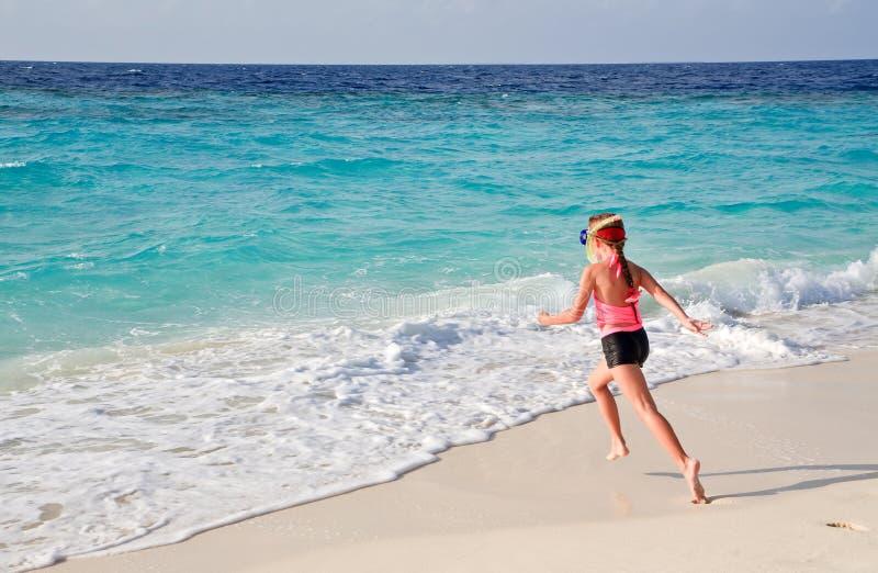 Kind dat aan oceaan loopt stock foto