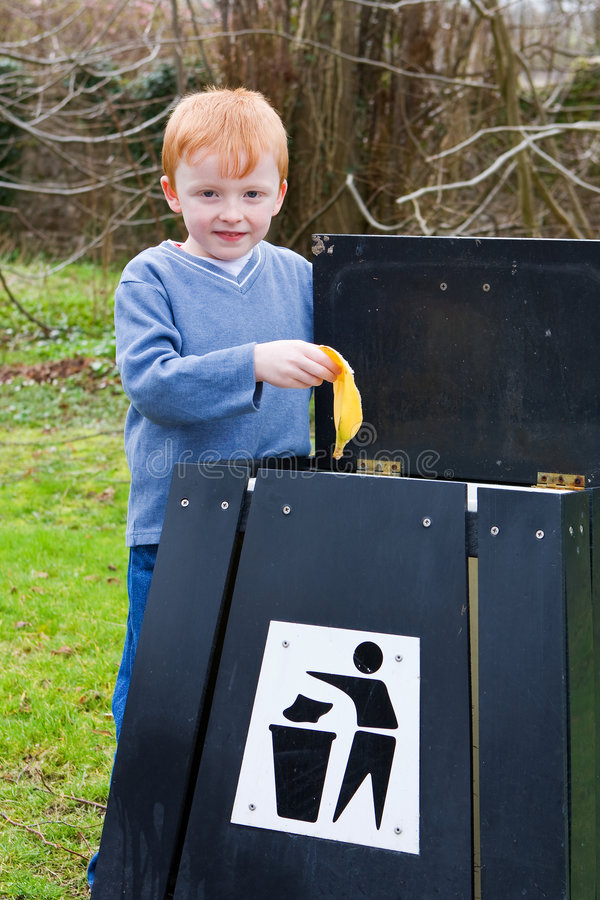 Kind dat afval in bak zet stock foto