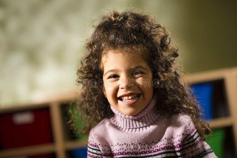Kind dat bij camera in kleuterschool glimlacht stock foto