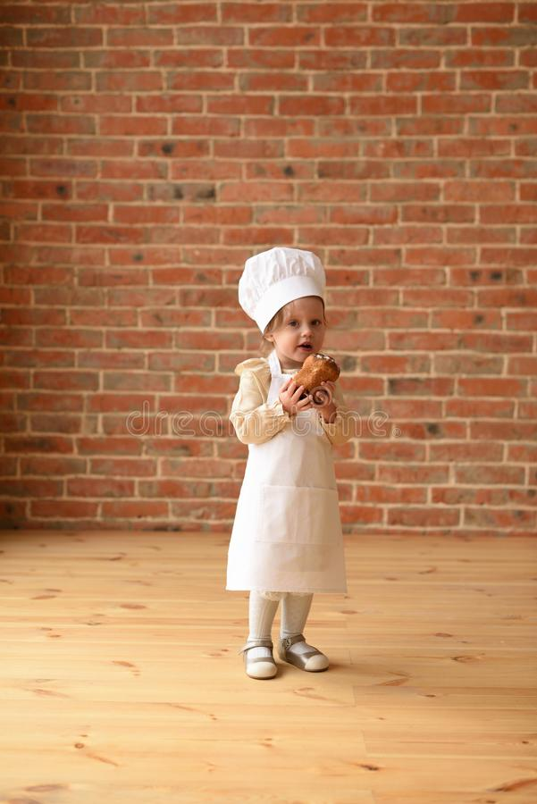 Kind dat chef speelt Cute toddler girl in chef-kok-apron en hoed die zoete kont eet aan de muur in een lege kamer stock fotografie