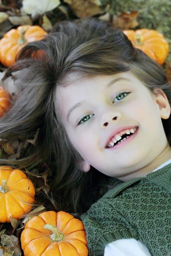 Kind dat in de Bladeren van de Herfst ligt stock afbeeldingen