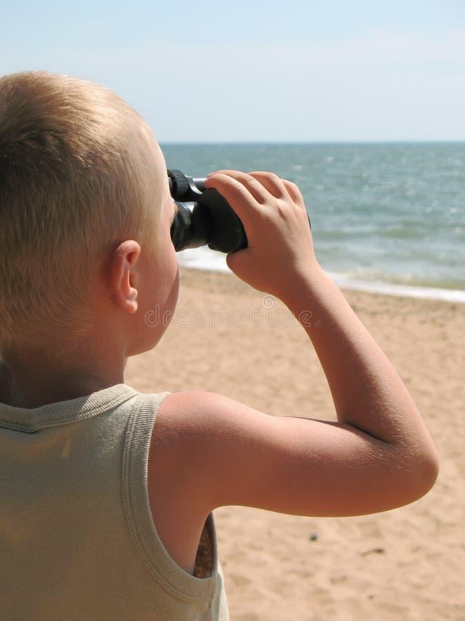 Kind dat door verrekijkers kijkt stock foto's
